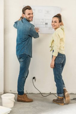 happy young couple holding blueprint at wall and smiling at camera in new house