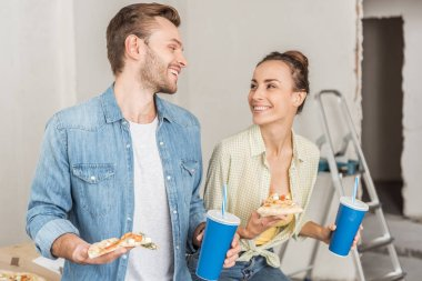happy young couple holding paper cups with drinking straws and pizza slices in new apartment