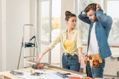 upset young couple standing near table with tools during house repair