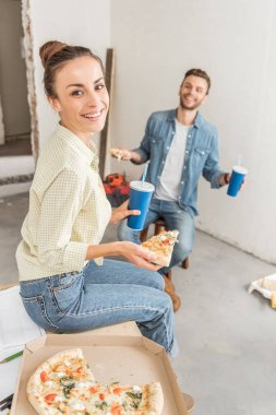 high angle view of happy girl smiling at camera while eating pizza with husband in new apartment