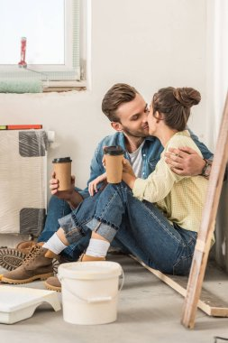 young couple holding paper cups and kissing while sitting on floor in new house