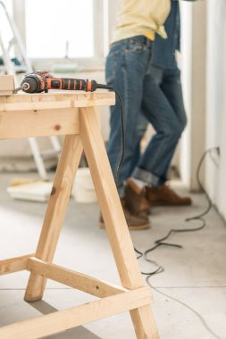 electric drill on wooden table and young couple standing near wall behind