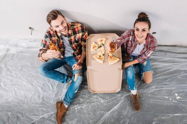 overhead view of happy young couple with beer and pizza sitting on floor and smiling at camera in new apartment