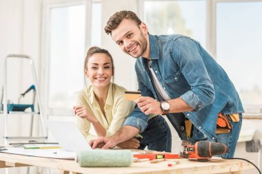 happy young couple with credit card smiling at camera during home improvement