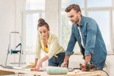 young couple looking at blueprint during house repair