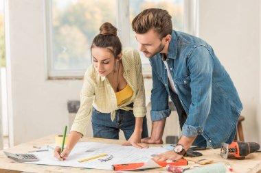 young couple marking blueprint and discussing renovation together