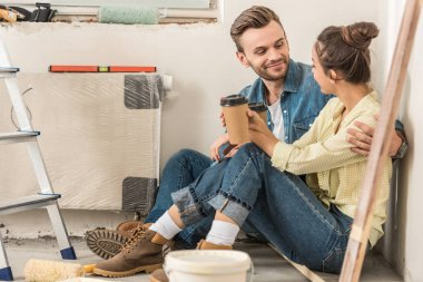 young couple holding paper cups and smiling each other while sitting on floor during house repair