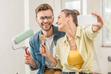 happy young couple holding tools and taking selfie with smartphone during house repair