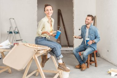 happy young couple holding pizza slices and paper cups during renovation
