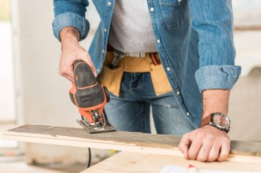 cropped shot of man using electric jigsaw while making repair at home