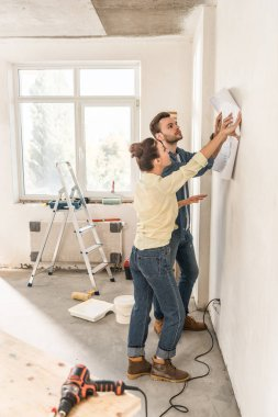 side view of young couple holding blueprint at wall during renovation