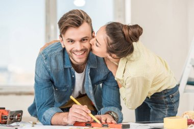 young woman kissing happy man marking blueprint with level tool