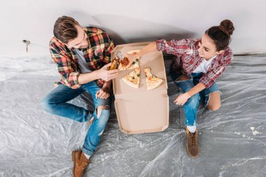 overhead view of young couple clinking beer bottles and eating pizza while sitting on floor in new apartment