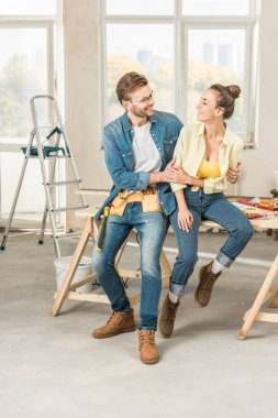 happy young couple hugging and smiling each other while sitting on table with tools