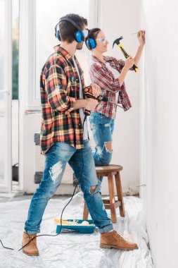 side view of young man holding electric drill and looking at smiling wife hammering nail in new apartment