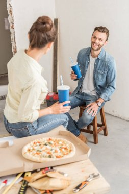 high angle view of young couple holding paper cups and eating pizza during break in repairment