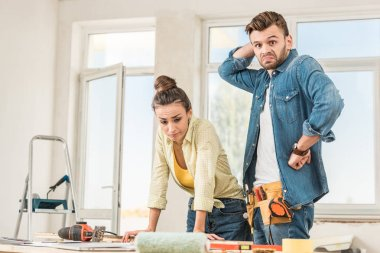 uncertain young couple standing near table with tools during repairment