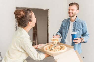 happy young couple holding box with pizza and paper cup with refreshing beverage in new apartment