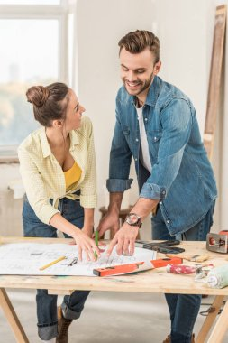 happy young couple discussing blueprint during renovation
