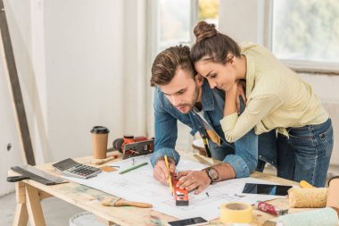 young woman looking at husband marking blueprint with level tool in new house