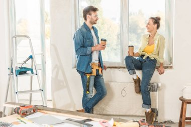 happy young couple holding coffee to go and smiling each other during repairment