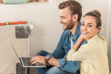 happy young man using laptop and beautiful wife smiling at camera in new house