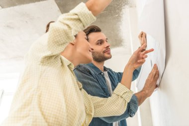 low angle view of smiling young couple holding blueprint at wall during repairment