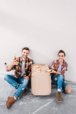 happy young couple eating pizza and drinking beer during break in repairment