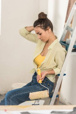 young woman sitting on step ladder and holding paint roller