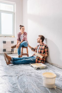 smiling young couple holding paint rollers and talking in new apartment