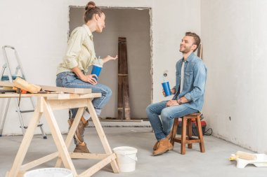 happy young couple holding paper cups and talking during repairment