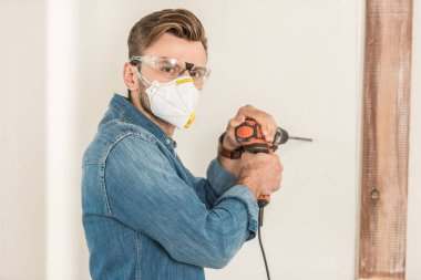 young man in protective workwear using electric drill and looking at camera during house repair