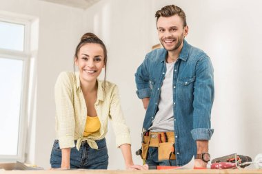 happy young couple leaning at table with tools and smiling at camera during house repairment