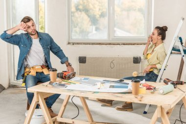 tired young couple sitting near table with tools during house repairment