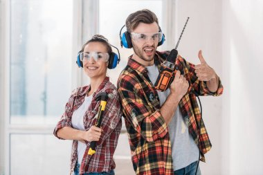 happy young couple in checkered shirts holding tools and looking at camera
