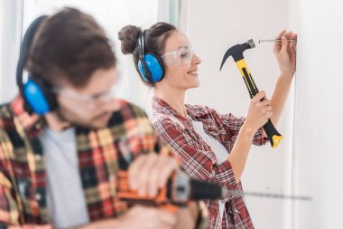 selective focus of young couple hammering and drilling wall during renovation