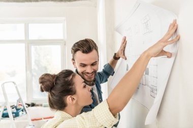 young couple holding blueprint at wall during renovation in new apartment