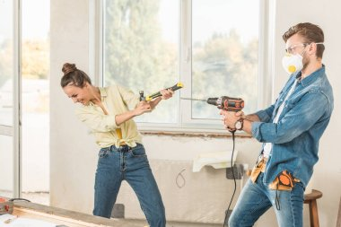 happy young couple having fun with tools during repairment in new apartment