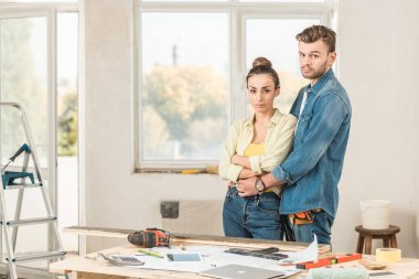 serious young couple embracing and looking at camera during house repairment