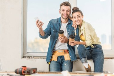 happy young couple with coffee to go and smartphone smiling at camera during renovation