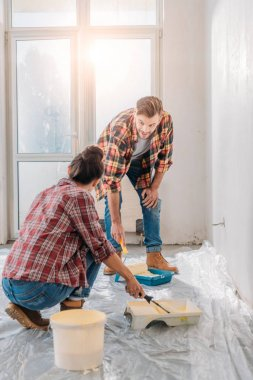 young couple in checkered shirts holding paint rollers and painting wall