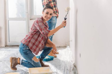 happy young woman painting wall and smiling at camera in new apartment