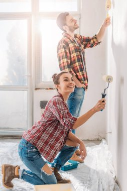 happy young couple painting wall with paint rollers in new apartment