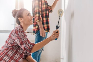 smiling young woman holding paint roller and painting wall