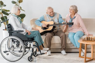 senior man sitting on sofa and playing acoustic guitar for women