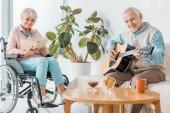 Fotografie Starší žena sedící na vozíku a čtení knihy, zatímco starší muž hraje na akustickou kytaru