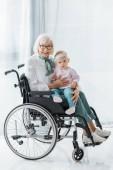 usmívající se babička vozíku drží malé vnučky