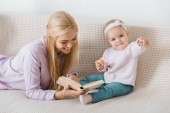 young happy mother laying on sofa and reading book to small daughter while toddler holding cookie