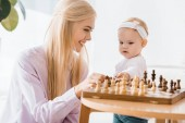 Fotografie young cheerful mother teaching daughter playing chess