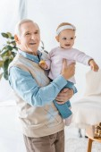 senior grandfather holding toddler granddaughter with cookie